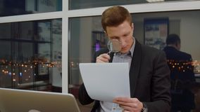 Ungt stiligt affärsmanläsningdokument till och med förstoringsapparaten lager videofilmer