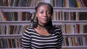 Ungt stiligt afrikansk amerikankvinnaanseende i arkiv och se kameran, allvarligt och fundersamt, bokhyllor stock video