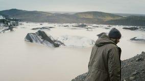 Ungt stiligt fotvandra för man som tar fotoet av den Vatnajokull islagun med glaciärer i Island på smartphonen arkivfilmer
