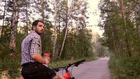 Ungt stiligt grabbsammanträde på cykeln och se omkring interestingly lager videofilmer