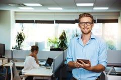 Ungt stiligt lyckat le för affärsman som rymmer minnestavlan, över kontorsbakgrund royaltyfria foton