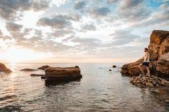 Ungt stiligt manidrottsman nenanseende på den steniga stranden Arkivbilder