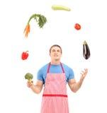 Ungt stiligt manligt bärande förkläde och jonglera med grönsaker Royaltyfri Fotografi