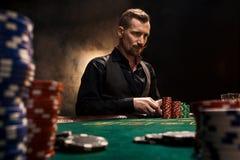Ungt stiligt mansammanträde bak pokertabellen med kort och chiper royaltyfria foton