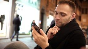 Ungt stiligt mansammanträde i kafét, i afton och att använda smartphonen i internet som spenderar tid bara arkivfilmer