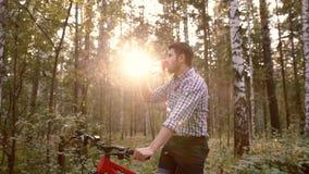 Ungt stiligt mansammanträde på cykeln och dricksvattnet stock video