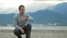 Ungt stiligt mansammanträde på den steniga stranden Han kontrollerar meddelanden på den smarta klockan Bak Stilla havet och lager videofilmer