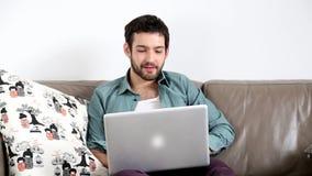 Ungt stiligt mansammanträde på soffan med bärbara datorn på varv arkivfilmer
