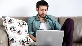 Ungt stiligt mansammanträde på soffan med bärbara datorn på varv lager videofilmer
