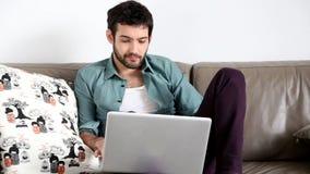 Ungt stiligt mansammanträde på soffan med bärbara datorn på varv stock video