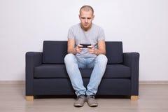 Ungt stiligt mansammanträde på soffan med mobiltelefonen royaltyfri bild