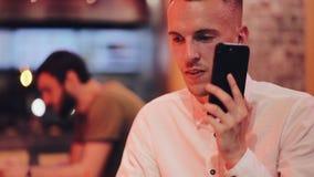 Ungt stiligt manvisartavlanummer och samtal på smartphonen i nattkafét Honom som sitter nära neonsignage arkivfilmer