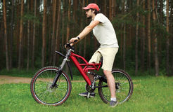 Ungt stiligt skäggigt mansammanträde på en cykel i skogen royaltyfri fotografi