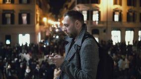 Ungt stiligt turist- mananseende i folkmassan i afton Manligt bruk smartphonen till fyndriktningen arkivfilmer