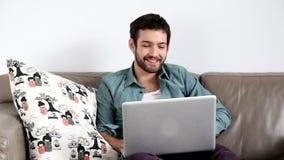 Ungt stiligt vuxet mansammanträde på soffan i vardagsrum och att ha video pratstund stock video