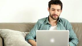 Ungt stiligt vuxet mansammanträde på soffan i vardagsrum och att ha video pratstund arkivfilmer