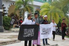 Ungt stolt med denislam flaggan Al Liwa Ar Roya Arkivbilder
