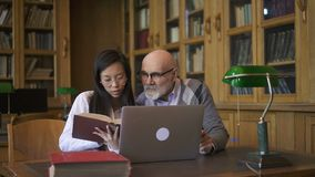 Ungt student- och biologprofessorsamtal som sitter på tabellen med bärbara datorn i arkiv lager videofilmer
