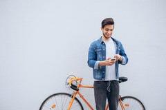 Ungt studentanseende nära cykeln som ser telefonen och lyssnar till musik Royaltyfri Fotografi
