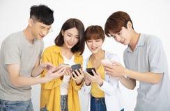 ungt studentfolk som håller ögonen på smartphonesna arkivbild