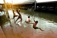 Ungt thailändskt folk som har gyckel i banhoppning för sommarpartidag in till kanalen Arkivbilder