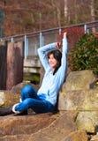 Ungt tonårigt flickasammanträde på stora stenblock eller vaggar utomhus, beväpnar lyftt över huvudet, upphetsat och lyckligt Royaltyfri Bild
