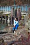 Ungt tonårigt flickasammanträde på stora stenblock längs sjökusten som ut ser över vatten Arkivbilder