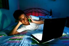 Ungt tonårigt framme av en bärbar datordator och på en säng och att använda en mobiltelefon eller en smartphone Royaltyfria Bilder