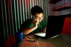 Ungt tonårigt genom att använda en mobiltelefon eller en smartphone framme av en bärbar datordator Royaltyfri Foto