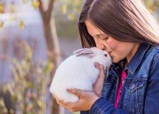 Ungt tonårigt innehav en vit kanin för behandla som ett barn som kysser det på pannan Arkivbild