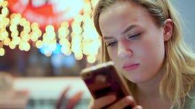 Ungt tonårigt meddelande för flickaläsningsmartphone som rynkar pannan Hon har matställen i ett kafé Snabbmat afton, på arkivfilmer