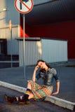 Ungt tonåringflickasammanträde på vägen utanför near stads- röd väggbakgrund i kjol och jeans klår upp på solnedgången Arkivfoton