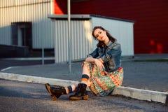 Ungt tonåringflickasammanträde på vägen utanför near stads- röd väggbakgrund i kjol och jeans klår upp på solnedgången Arkivbilder