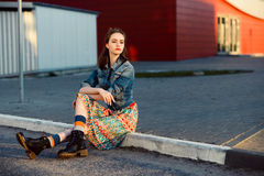 Ungt tonåringflickasammanträde på vägen utanför near stads- röd väggbakgrund i kjol och jeans klår upp på solnedgången Royaltyfri Bild
