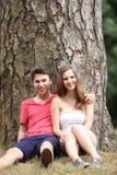 Ungt tonårs- parsammanträde mot ett träd Arkivfoton