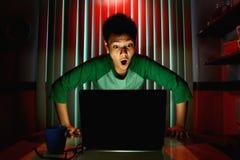 Ungt tonårigt agera som är förvånat framme av en bärbar datordator Arkivbilder