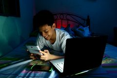 Ungt tonårigt framme av en bärbar datordator och på en säng och att använda en minnestavla Arkivbilder
