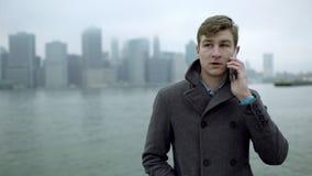 Ungt turist- samtal över en smartphone nära Hudson River stock video