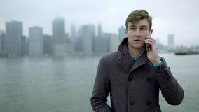 Ungt turist- samtal över en smartphone nära Hudson River lager videofilmer