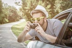 Ungt turist- tagande foto från bilen, genom att använda den retro kameran Arkivfoto