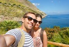 Ungt turist- tar ett selfieminnesfoto i tropiskt landskap under semester runt om italienska kuster le för par Royaltyfri Fotografi