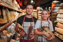 Ungt upptagen förpacka för man- och kvinnahåll av pasta i händer i livsmedelsbutik De ser på kamera och leende Positivt trevligt arkivbilder