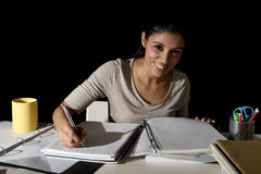 Ungt upptaget härligt spanskt le för flicka som är lyckligt och som är säkert studera hemma sent - natt Fotografering för Bildbyråer
