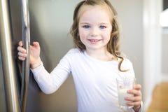 Ungt vitt dricka för flicka som är nytt, mjölkar från ett exponeringsglas, medan stå framme av det öppna kylskåpet Arkivbilder