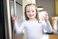 Ungt vitt dricka för flicka som är nytt, mjölkar från ett exponeringsglas, medan stå framme av det öppna kylskåpet Arkivfoto
