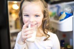 Ungt vitt dricka för flicka som är nytt, mjölkar från ett exponeringsglas, medan stå framme av det öppna kylskåpet Arkivbild