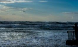 Ungt vuxet tagande foto av fantastiskt färgrikt solnedgångljus på stranden Arkivbilder
