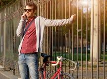 Ungt vuxet tillfälligt klätt kalla på telefonen i stadsgatan Arkivfoto