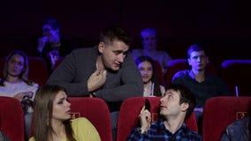 Unhöflicher Mann, der am Telefon im Kino und andere Besucher behindern spricht stock video