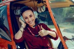Unha do polegar fêmea bonita alegre da exibição do piloto e felicidade expressar imagens de stock royalty free